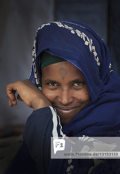 Portrait of smiling Amhara woman wearing blue traditional clothing  Ethiopia  Africa