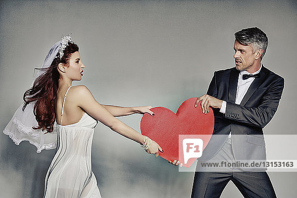 Bride and bridegroom fighting over heart