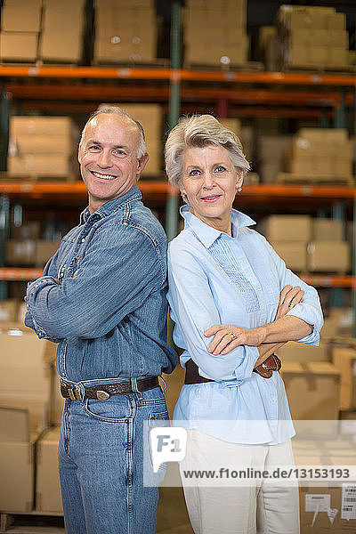 Portrait of warehouse workers back to back