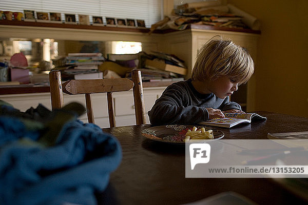 Young boy sitting at kitchen table reading book