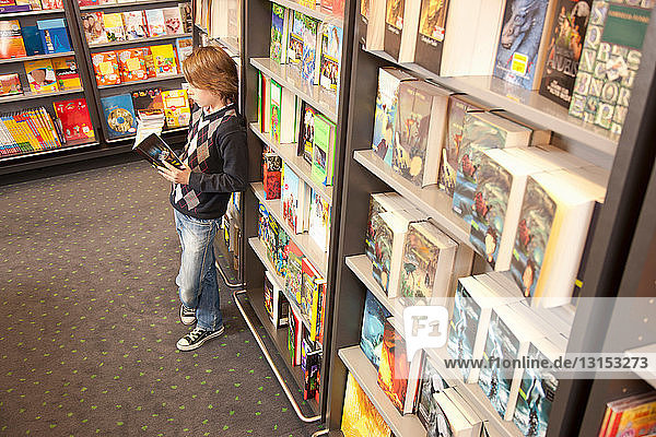 Boy leaning against bookcase reading