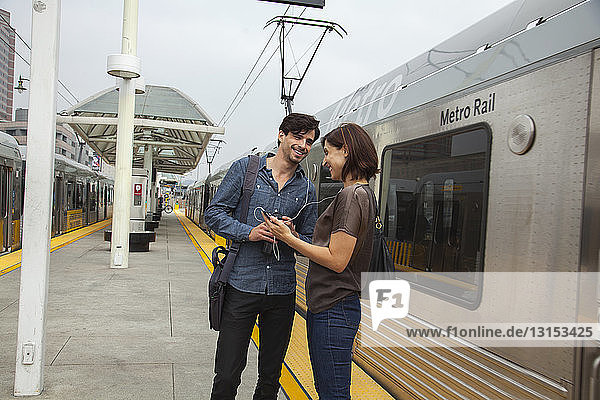 Couple listening to shared earphones at station  Los Angeles  California  USA