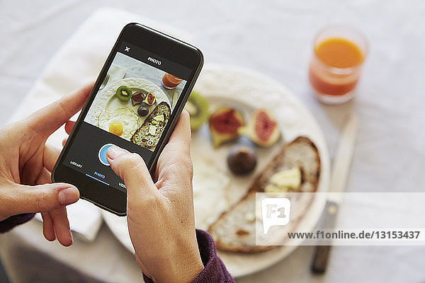 Over shoulder view of woman photographing breakfast table on smartphone