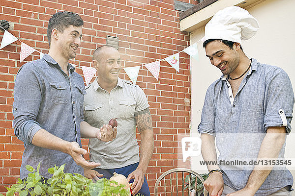 Male friends laughing at chef's hat whilst preparing food for garden barbecue