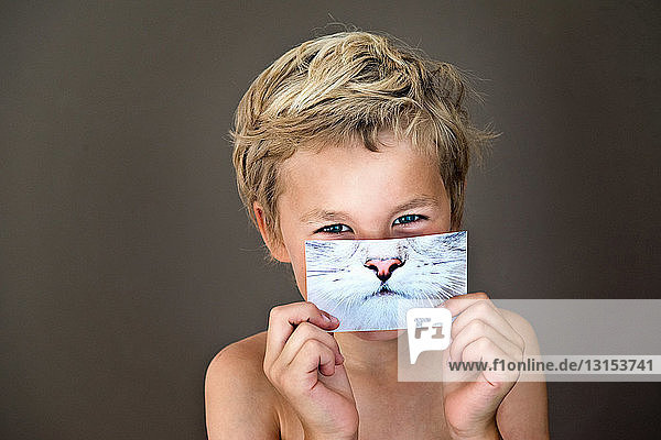 Boy holding picture of cat over face