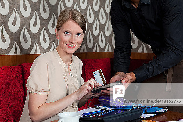 Woman paying waiter with card in cafe