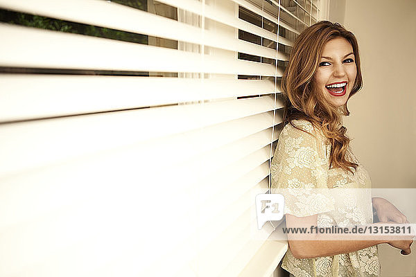 Portrait of beautiful young woman laughing in front of venetian blind