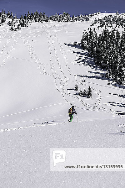 Male skier walking up snow covered mountain  Spitzingsee  Germany