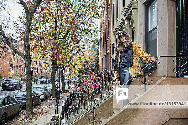 Portrait of stylish young woman posing on steps outside house