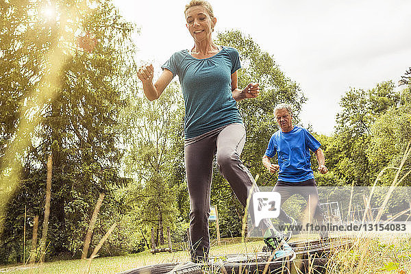 Mature woman and senior man on assault course