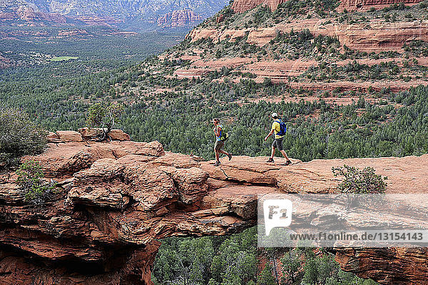 Hiking couple on arched rock formation  Sedona  Arizona  USA