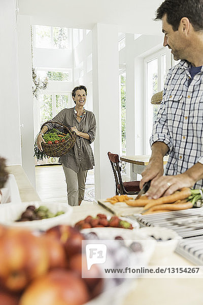 Couple carrying and preparing fresh vegetables in kitchen