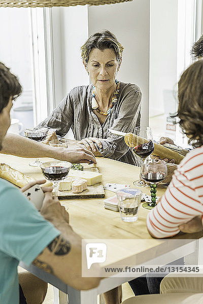 Adult friends playing cards and drinking wine at dining table