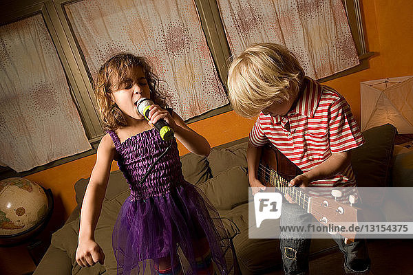 Girl singing with microphone with boy playing guitar