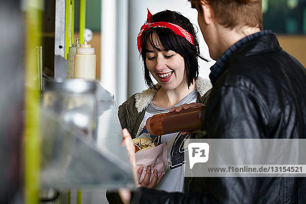 Couple eating food cart sandwich