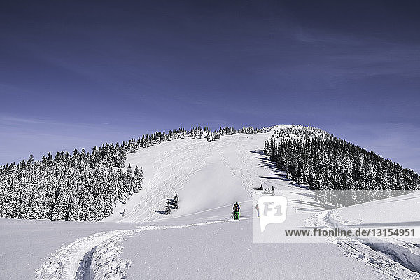 Distant view of two male skiers walking up snow covered mountain  Spitzingsee  Germany