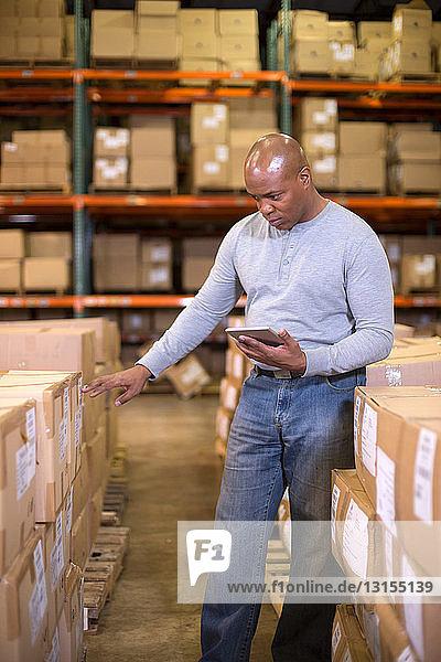 Male warehouse worker using digital tablet