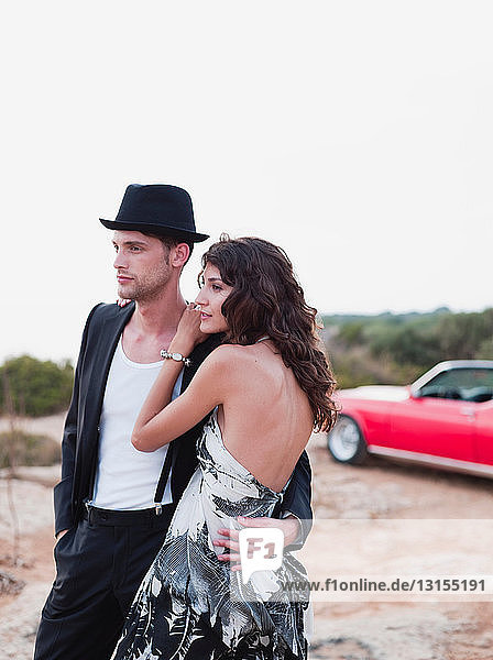 couple standing in front of vintage car
