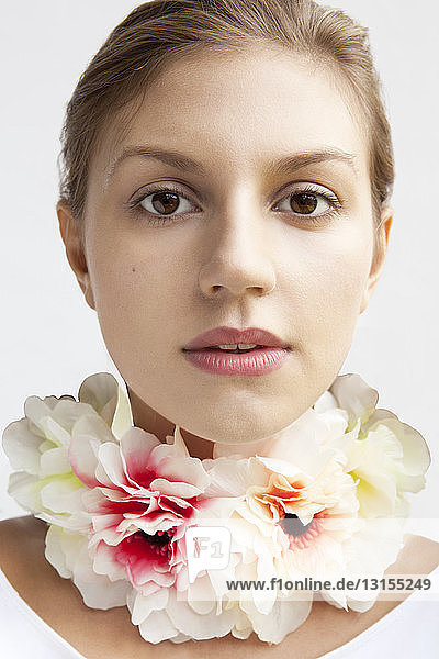 Studio portrait of beautiful young woman wearing flower necklace
