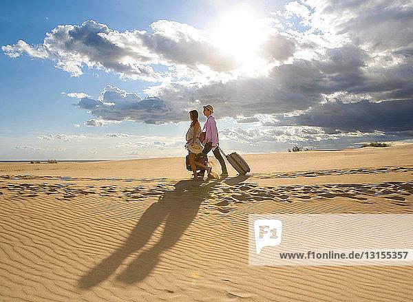 Traveling couple walking on sand