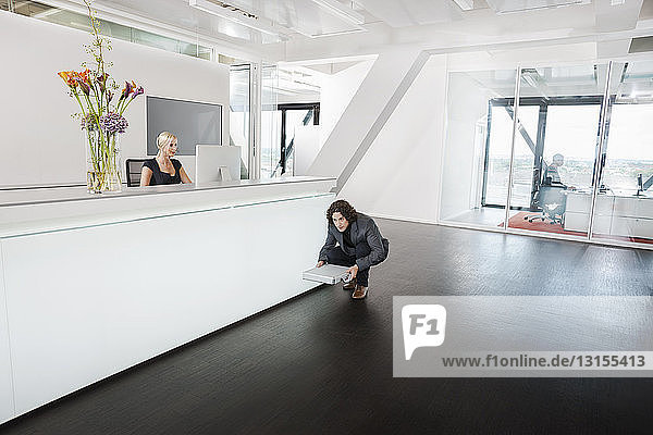 Man crouching in front of reception desk with briefcase