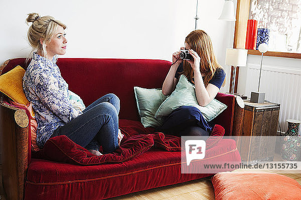 Young women sitting on sofa  taking photograph