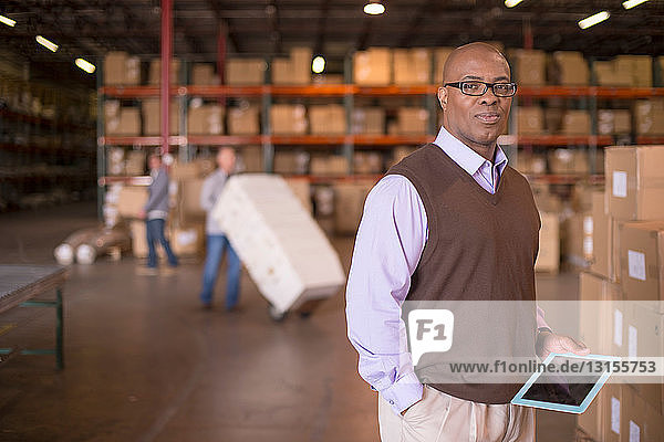 Portrait of warehouse manager with digital tablet