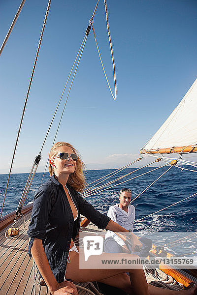 couple steering a sailing boat
