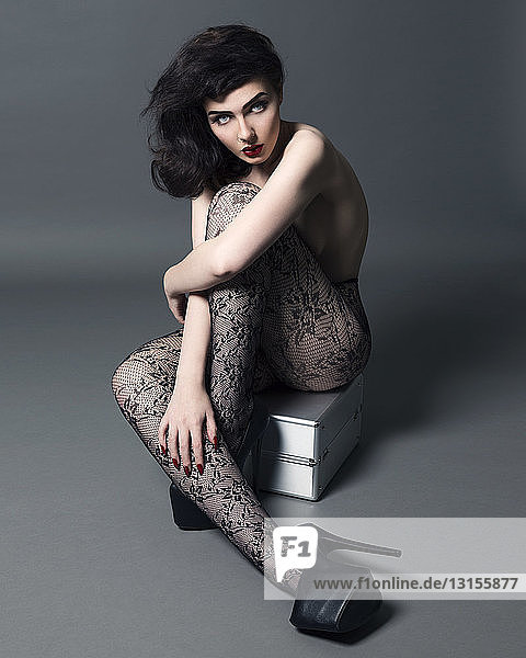 Portrait of young woman  wearing tights and high heeled shoes  sitting on vanity case