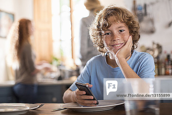 Teenage boy holding smartphone at dining table