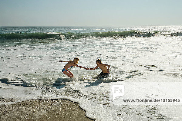 Couple helping each other in surf