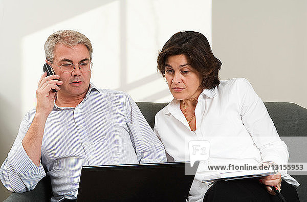 Mature couple working together on laptop