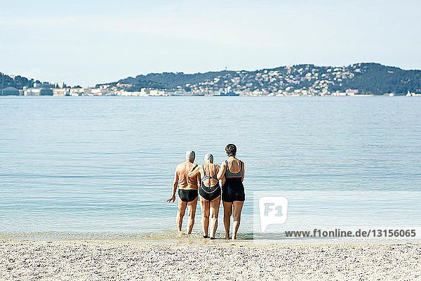 Three senior friends walking into the sea  rear view