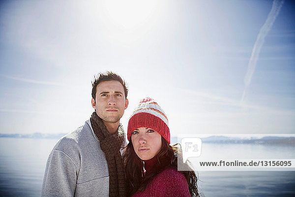Couple looking into distance by lake