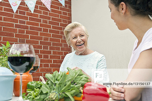 Two women chatting while preparing food at garden table