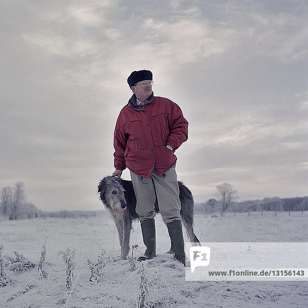Portrait of man with deerhound in snow covered field Portrait of man with deerhound in snow covered field