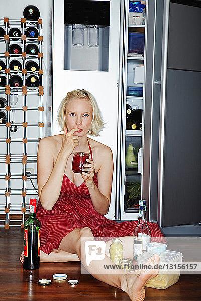 Woman eating on floor by fridge