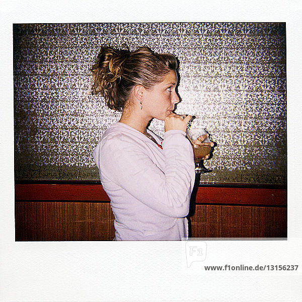 Instant film photograph of woman drinking drink