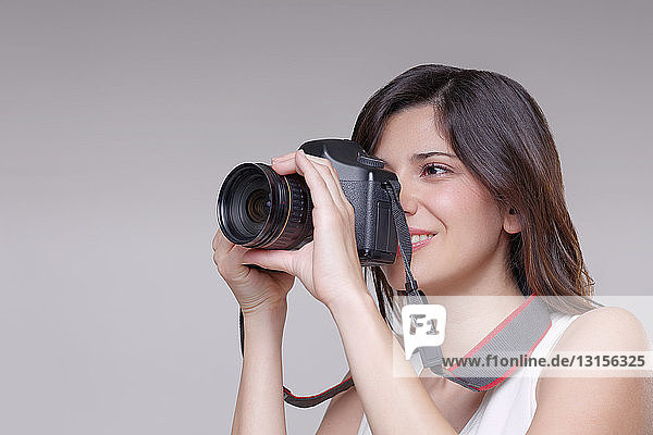 Young woman taking photograph with digital SLR camera