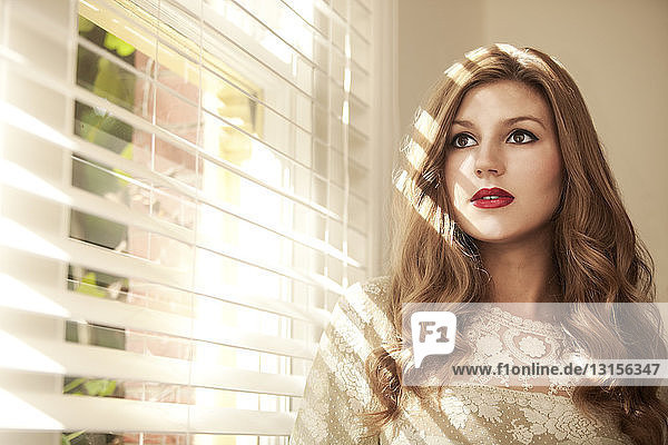 Glamorous young woman staring out of window with venetian blind
