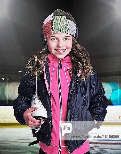 Smiling girl holding ice skate in rink Smiling girl holding ice skate in rink