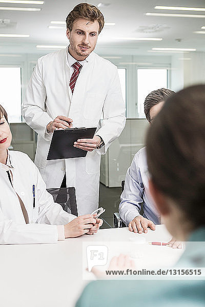 Man wearing lab coat holding clipboard  colleagues in foreground