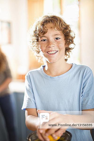 Teenage boy juicing orange in kitchen