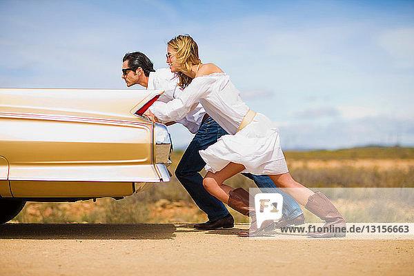 Couple pushing a car