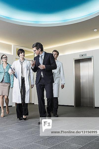 Four mid adults walking through lobby