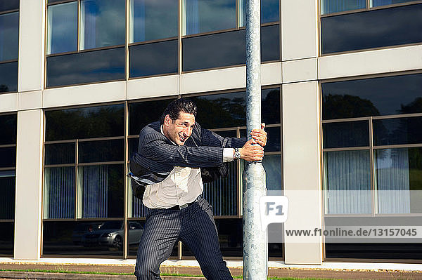 Business man clinging to a lamp post