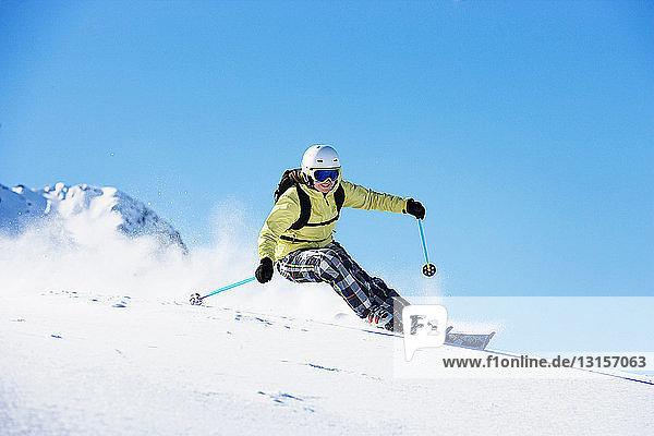 Female skiing down mountainside