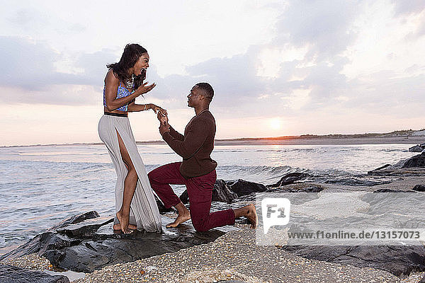 Mid adult man kneeling on rocks beside sea  proposing to young woman