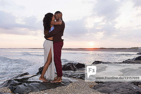 Couple standing on rocks beside sea  hugging  face to face