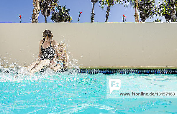 Mother and son sitting splashing in swimming pool,  Los Angeles,  California,  USA
